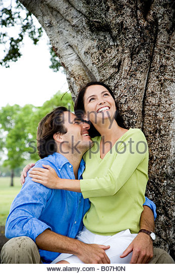 couple embracing in front of tree - Stock Image