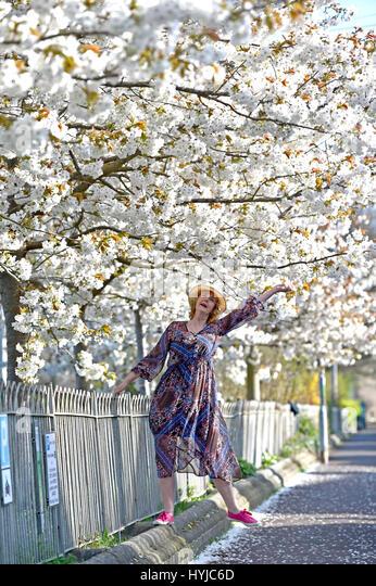 Brighton, UK. 5th Apr, 2017. A woman enjoys the beautiful Spring blossom around Queens Park in Brighton on a warm - Stock-Bilder