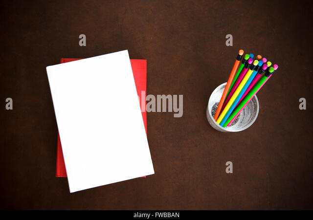 Writer desktop symbol with empty cover books and colorful pencils on wood - Stock Image