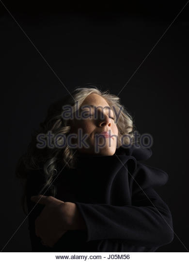 Portrait serene woman with eyes closed against black background - Stock Image