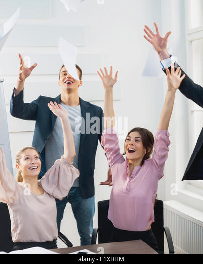 Businesspeople throwing papers in the air at office - Stock Image