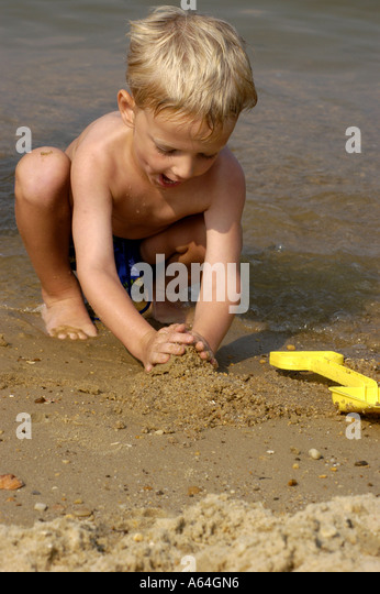 Young boy playing on beach digging in sand family summer vacation - Stock Image