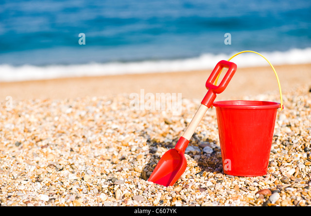 Red Childrens Toy Bucket and Spade on the Beach - Stock Image