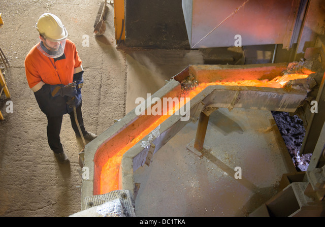 Worker monitoring molten metal at aluminum recycling plant - Stock Image