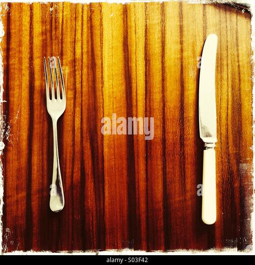 Knife and fork on highly polished stylish wood grain retro 1960's dining table - Stock Image