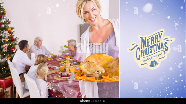 Composite image of proud mother showing roast turkey - Stock Image