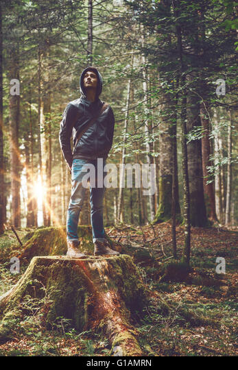 Confident young man standing in the forest, freedom and individuality concept - Stock Image