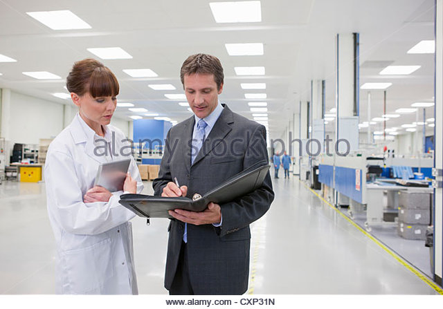 Scientist and businessman looking at paperwork in hi-tech manufacturing plant - Stock Image