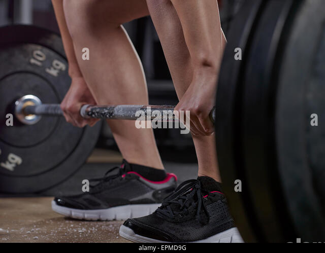 Close-up of young woman doing weightlifting with barbell - Stock Image