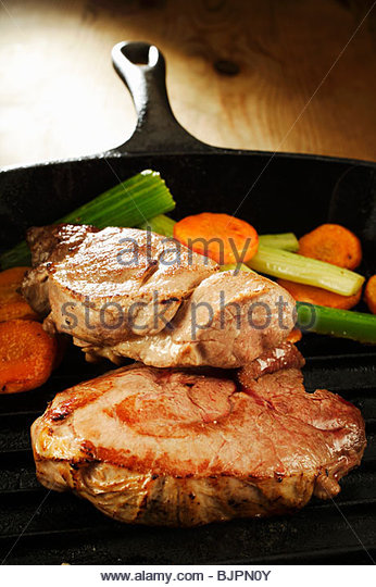 Wild boar steaks with vegetables in grill pan - Stock Image