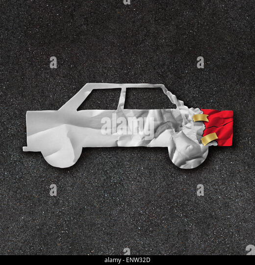 Car repair accident symbol and automobile crash fix concept on an asphalt road with  white crumpled paper shaped - Stock Image