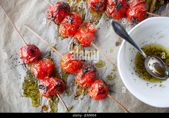Grilled tomato skewers and toasted baguette - Stock Image