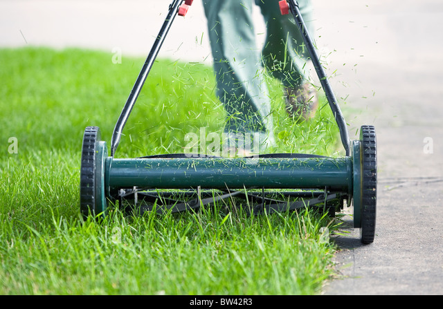 Woman cutting grass with an environmentally friendly push lawn mower, Winnipeg, Manitoba, Canada - Stock Image