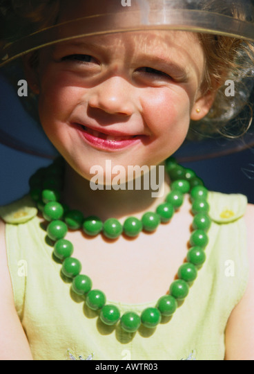 Little girl playing dress-up, smiling, portrait - Stock Image