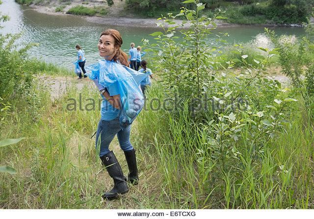 Portrait of smiling volunteer carrying garbage bag - Stock Image