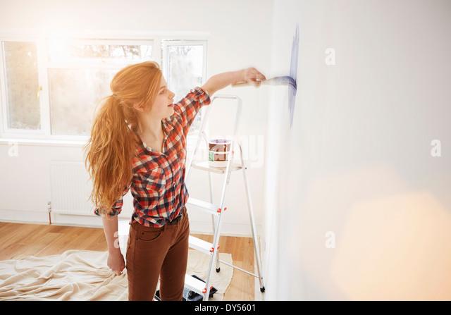Teenage girl painting her bedroom wall - Stock Image