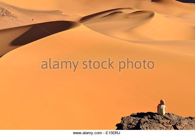 Algeria, Tassili n' Ajjer, Tadrart, Sahara, Tassili n' Ajjer National Park, woman looking to sand dunes - Stock Image