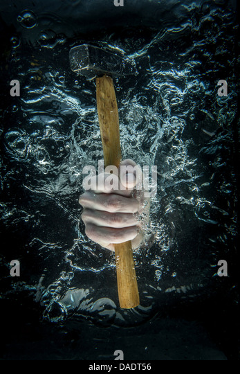 Male hand gripping hammer beneath water - Stock Image