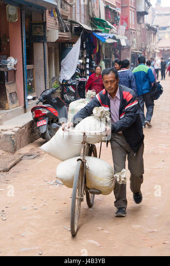 Nepalese man delivering a heavy load on his bike in Bhaktapur, Nepal. - Stock Image