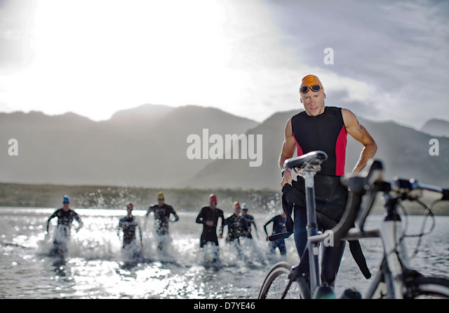 Triathletes emerging from water - Stock Image