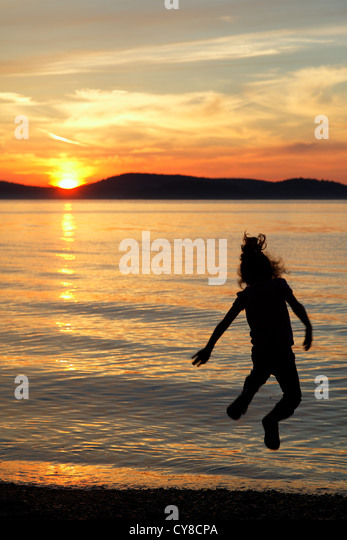 Girl leaping into the air above the setting sun, Sunset Beach, Washington Park, Anacortes, Skagit County, Washington - Stock Image