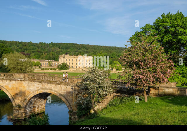 Couple stood on the bridge at Chatsworth with the house in the background - Stock Image