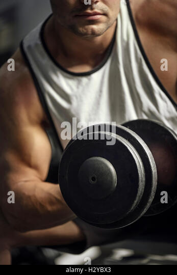 Athletic strong sportsman having a weightlifting training - Stock Image