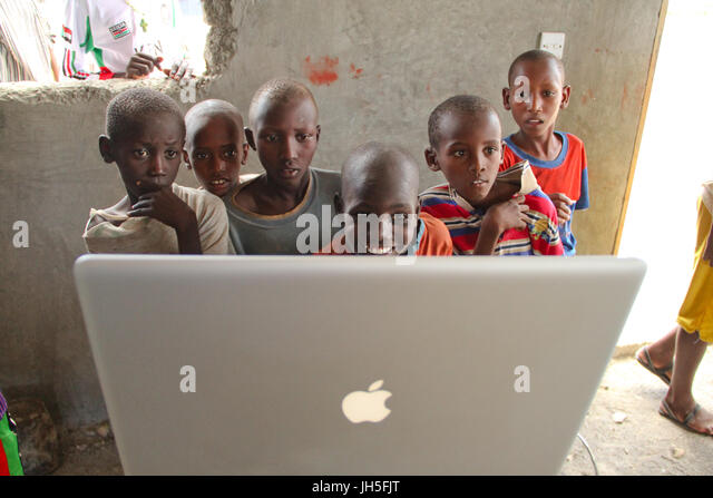 Loiyangaleni, Kenya. 19th May 2012. Turkana children maze at images and video an apple laptop during a rehearsal - Stock Image