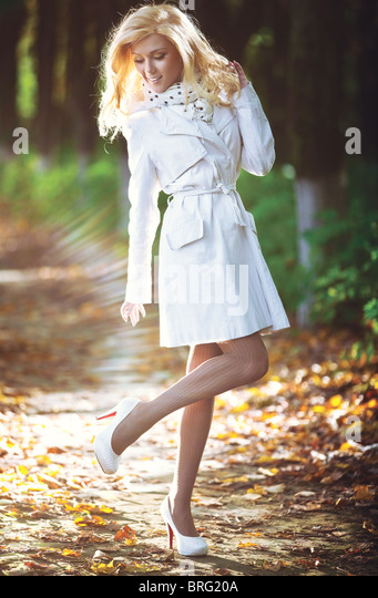 Young woman walking in autumn park. Light shine effect. - Stock Image