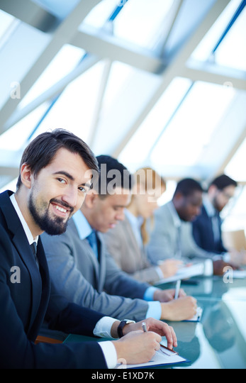 Row of business people listening to presentation at seminar with smiling young man on foreground - Stock Image