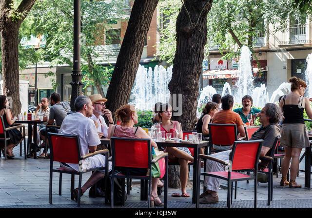 Madrid Spain Europe Spanish Centro Lavapias Calle Argumosa restaurant alfresco tables customers Hispanic man woman - Stock Image