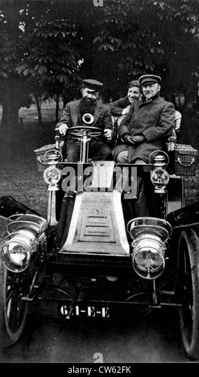 Tristan Bernard behind wheel Renault car Jules Renard sitting next to him at back Lucien Guitry's son Sacha - Stock Image