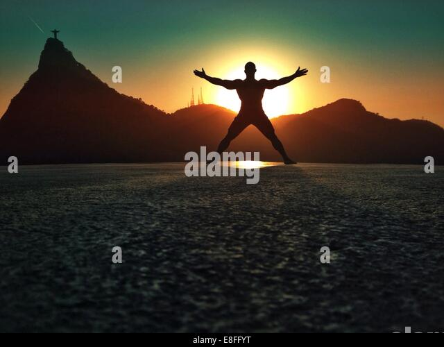silhouette of man messing about on beach at sunset, Rio de Janeiro, Brazil - Stock Image