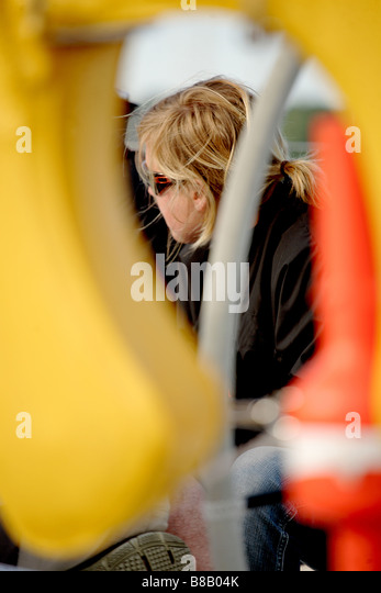White,European female sailor framed by part of a sailing yacht - Stock Image