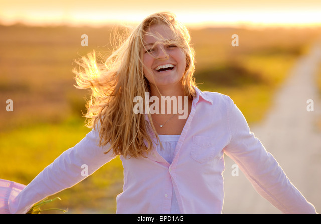 Young happy woman standing on country road - Stock Image