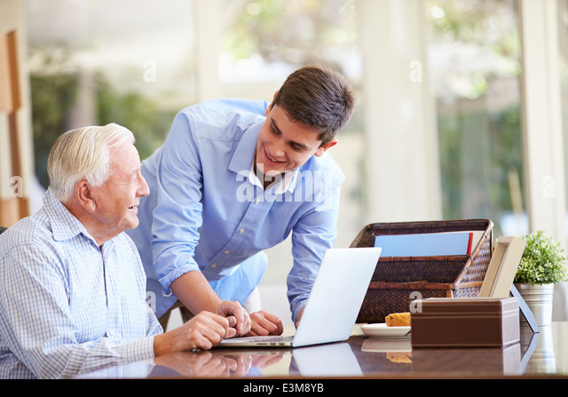 Teenage Grandson Helping Grandfather With Laptop - Stock-Bilder