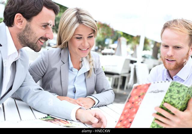Businesspeople deciding menu at sidewalk cafe - Stock Image