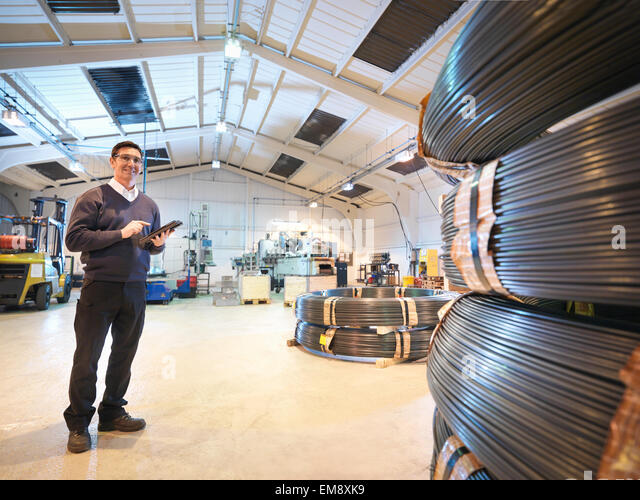 Engineer with digital tablet in automotive parts factory, portrait - Stock Image