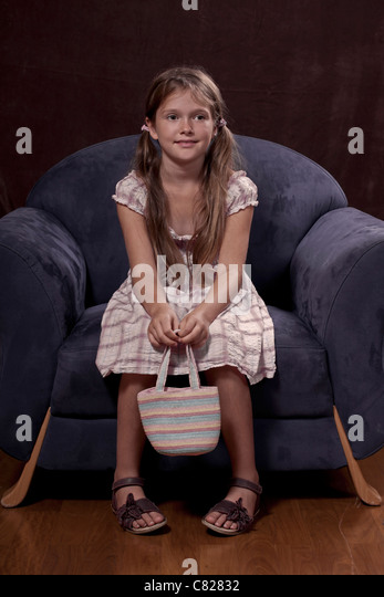 eight year old girl sitting on a chair and holding a handbag - Stock Image