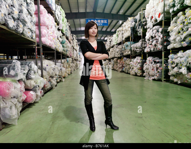 A portrait of a young woman inside a warehouse surrounded by thousands of rolls of fabric. - Stock Image