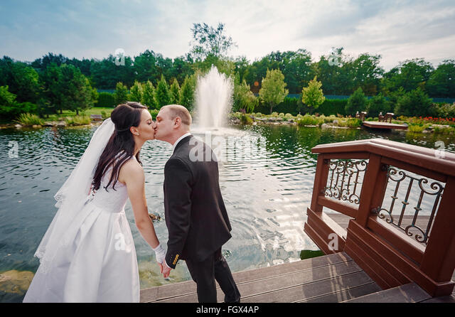 groom and the bride walk near the lake on their wedding day - Stock Image