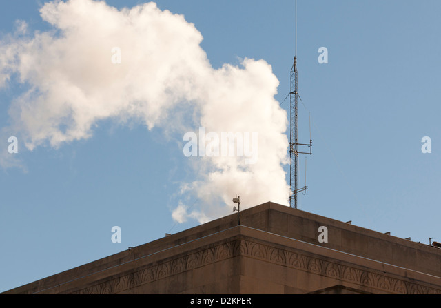 Steam rising from atop a building - Stock Image
