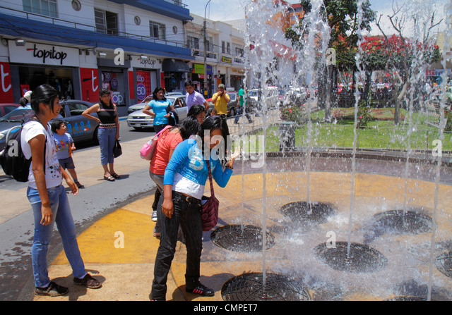 Peru Tacna Avenida San Martin Plaza de Armas interactive water feature fountain water jet spout Hispanic girl teen - Stock Image