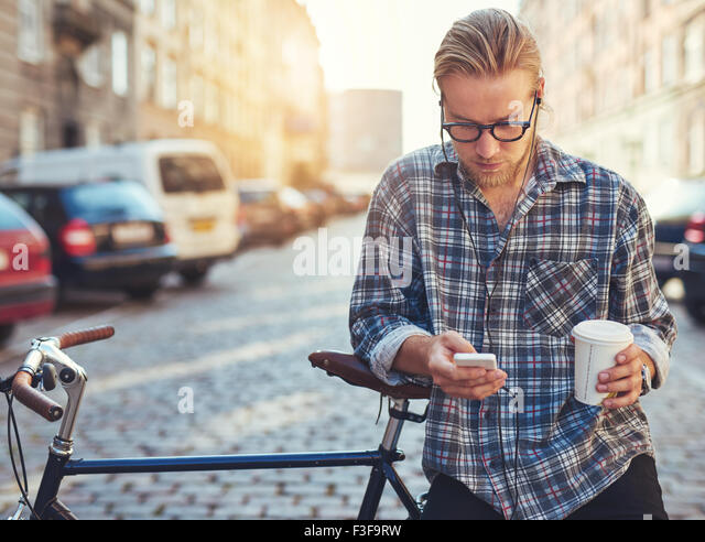Outdoor portrait of modern young man with mobile phone in the street, sitting on bike - Stock-Bilder