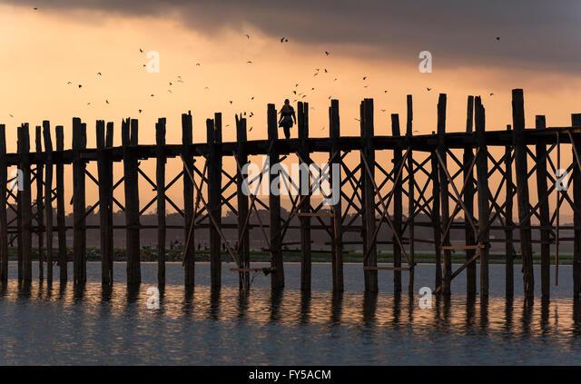 Sunrise over the U Bein Bridge crossing the Taungthaman Lake, the longest teakwood footbridge in the world - Stock-Bilder