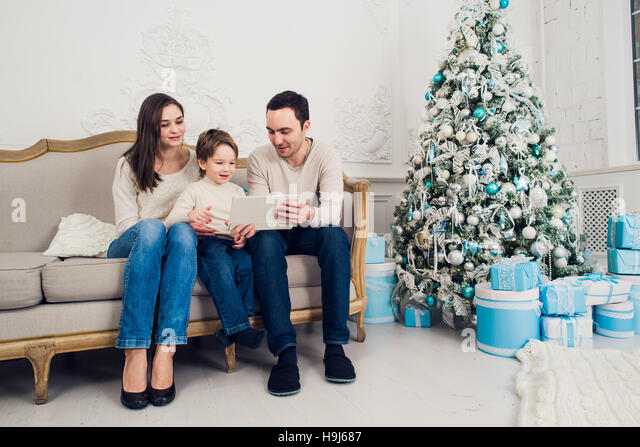 Cheerful family sitting in the living room having fun with the digital tablet that Santa Claus brought her, behind - Stock Image