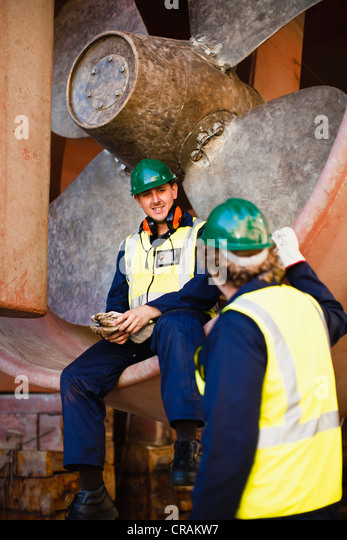 Workers talking in propeller on dry dock - Stock Image