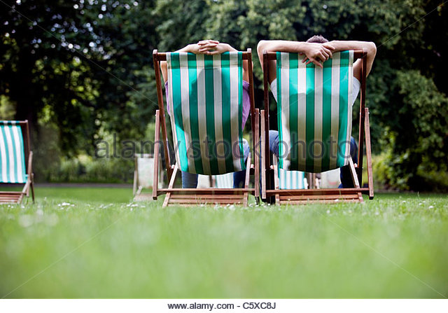 A young couple sitting on deckchairs in St James Park, rear view - Stock-Bilder