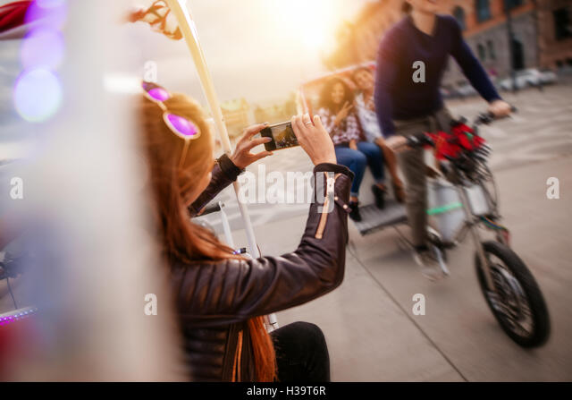 Woman photographing friends riding tricycle on road. Young people on tricycle on city street. - Stock Image