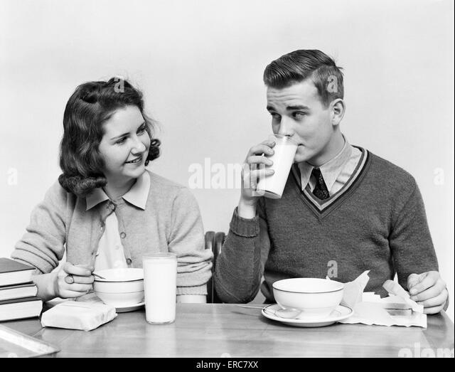 1940s TEENAGE GIRL AND BOY EATING SCHOOL    LUNCH SOUP SANDWICHES TOGETHER BOY DRINKING MILK - Stock Image
